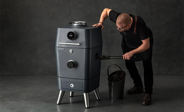 Heston Blumenthal loading charcoal into a 4K BBQ against a grey backdrop.